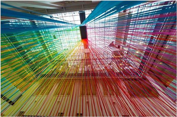 カラーテープでつくられた巨大な虹のようなインスタレーションが幻想的